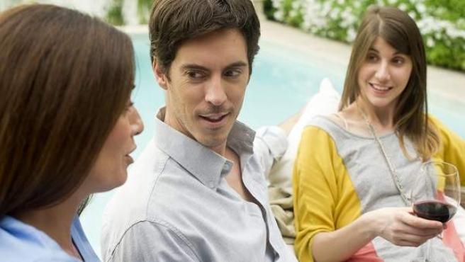 Tres amigos manteniendo una conversación.