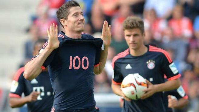 El delantero polaco del Bayern de Múnich Robert Lewandowski celebra su gol ante el Mainz y muestra una camiseta con el número de goles que lleva en la Bundesliga.