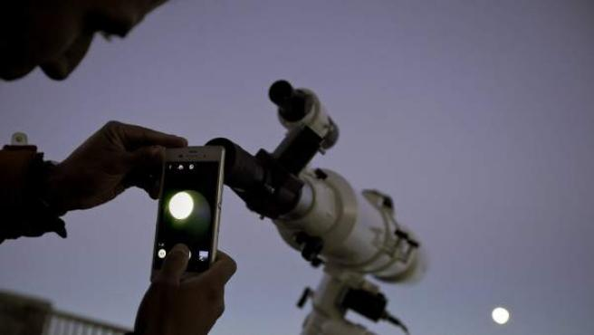 Un hombre fotografía, a través de un telescopio, la superluna desde el volcán Teide en Tenerife.