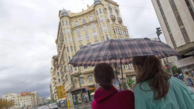 Dos jóvenes se protegen de la lluvia en Valencia.