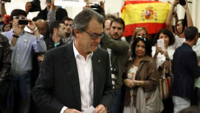 El presidente de la Generalitat y número cuatro en las listas de Junt pel Sí, Artur Mas, votando en las elecciones de Cataluña mientras varios miembros de VOX exhiben una bandera de España en la mesa electoral donde acudió a votar.