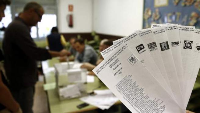 Una persona muestra las papeletas de los diferentes partidos que concurren a las elecciones al Parlamento Catalan que se celebran en Cataluña, mientras una persona deposita su voto en la urna en una jornada en la que un total de 5.314.736 personas están llamadas a votar, a las que se suman los 196.062 residentes en el extranjero.