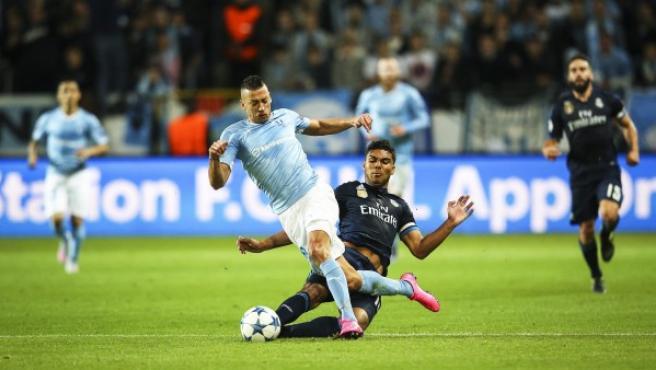 El centrocampista brasileño del Real Madrid, Casemiro (d) lucha por el balón con Nikola Djurdjic (i) del Malmoe.