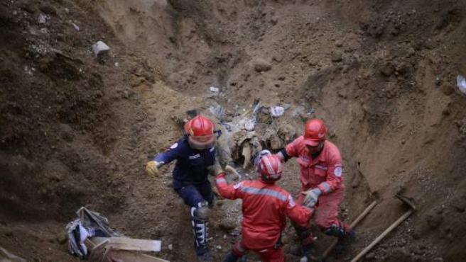 Bomberos huyendo de una pila de tierra que se desliza durante un rescate en Santa Catarina Pinula (Guatemala), después de un deslave en la zona.