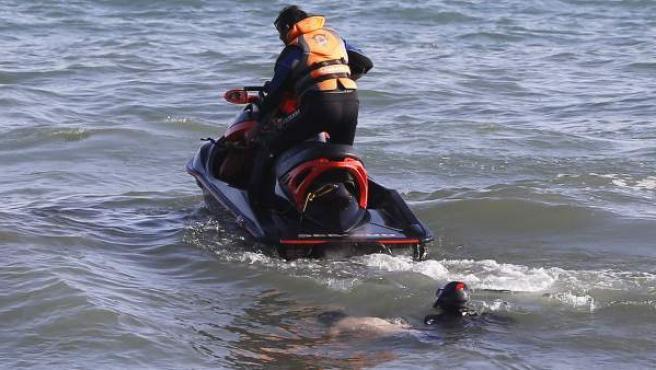Momento en el que efectivos de Protección Civil encuentran en el agua el cuerpo del tercer ahogado en la playa La Venus de Marbella (Málaga).