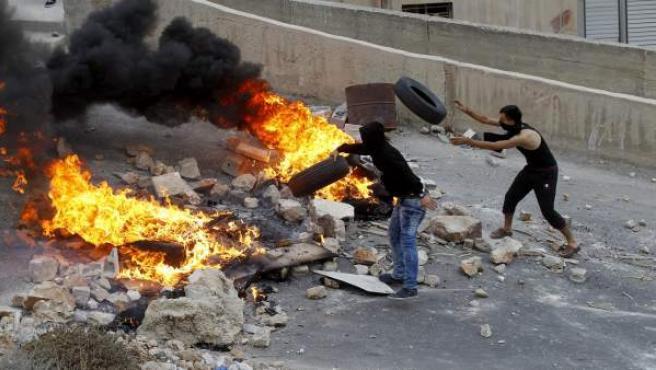 Palestinos lanzan neumáticos a una barricada en llamas durante los enfrentamientos con soldados israelíes tras una redada en la ciudad de Nablus (Cisjordania).