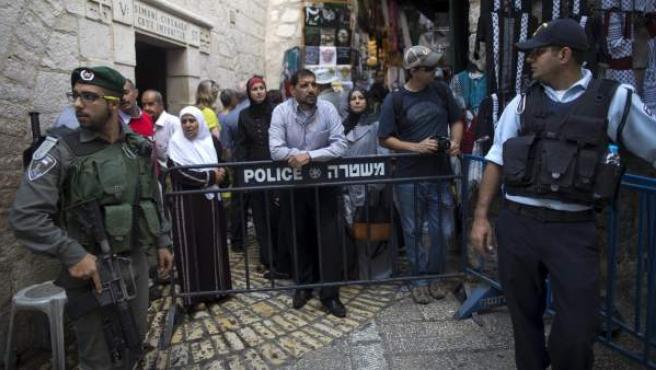 Varios palestinos esperan tras una valla colocada por la policía en el casco viejo de Jerusalén (Israel).