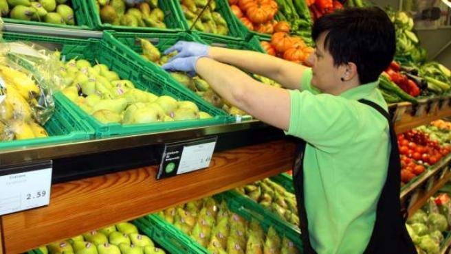 Una trabajadora de una cadena de supermercados coloca bien las peras en la zona de frutería.