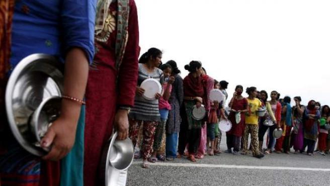 Nepalíes hacen cola para recoger alimentos en un campo de refugiados de Katmandú.