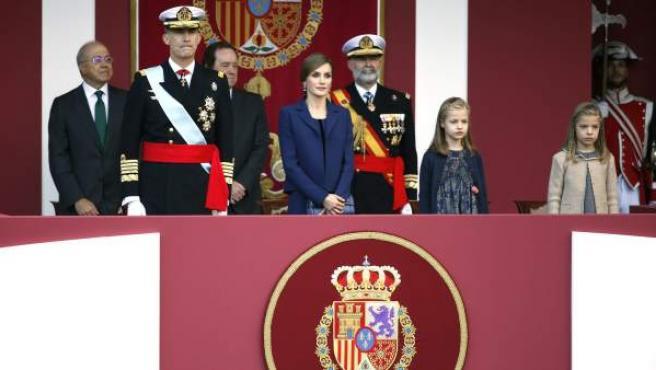 Los Reyes, acompañados de la princesa Leonor (izda.) y la infanta Sofía, presiden en la plaza de Cánovas del Castillo, Madrid, el desfile del Día de la Fiesta Nacional.