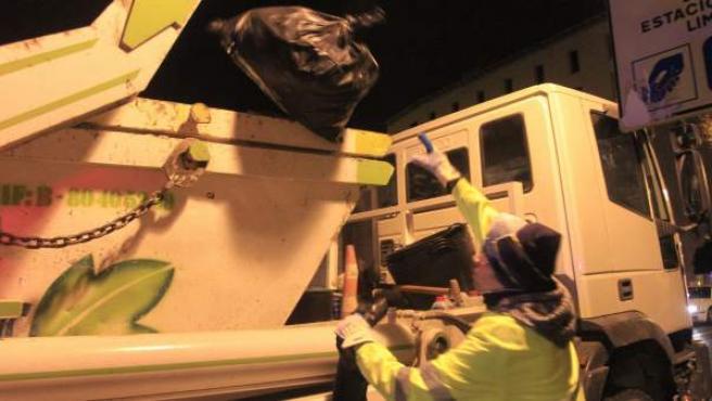 Un operario de Tragsa carga un camión con una bolsa de basura tras la salida de los camiones de esta empresa pública para cumplir con los servicios mínimos de la huelga de limpieza en Madrid.