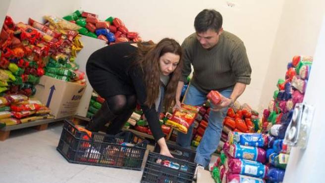 Irene y Jose rellenan las cestas en la despensa del Banco de Alimentos en el barrio de Tetuán, en Madrid.
