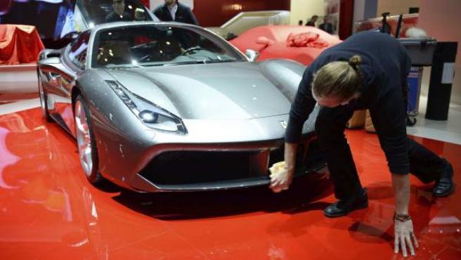 Una empleada saca brillo a la carrocería de un Ferrari 488 GTB en la víspera de la apertura para la prensa de la 85 edición del Salón del Automóvil de Ginebra en las salas del recinto ferial Palexpo en Ginebra5.