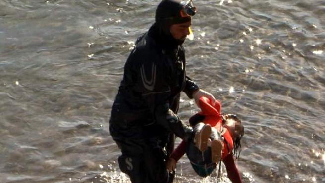 Un miembro de la Guardia Costera saca del agua el cuerpo de una niña refugiada hallada en la costa de la isla de Lesbos, Grecia.