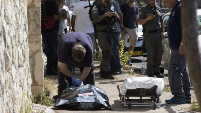 Trabajadores de una funeraria transportan el cuerpo de un joven palestino de 16 años fallecido en una colonia judía de Jerusalén Este a manos de las fuerzas israelíes.