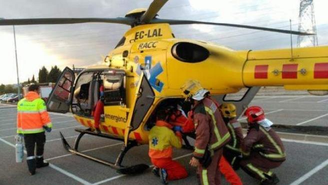Miembros de emergencia trasladan al joven herido en helicóptero.