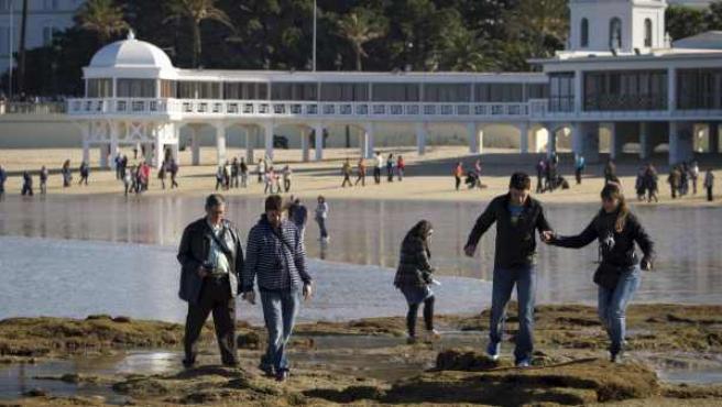Varias personas caminan por unos islotes de la Playa de la Caleta (Cádiz) durante una gran marea baja.