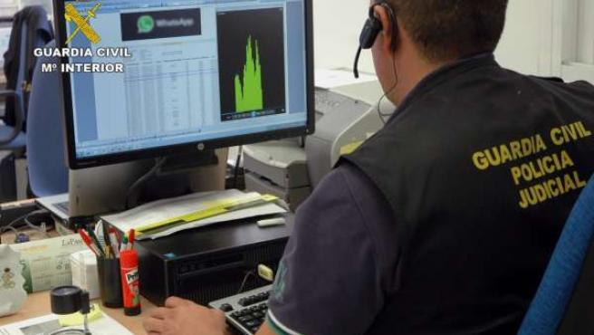 Un agente de la Guardia Civil delante de un ordenador decomisado