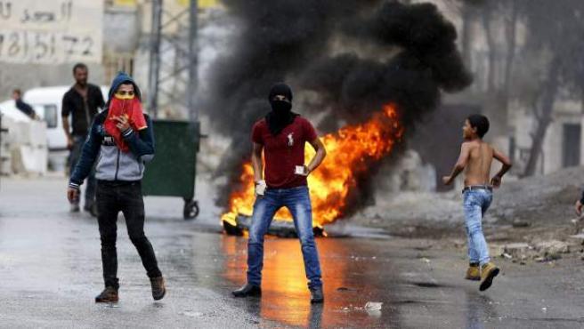 Un grupo de jóvenes palestinos lanzan piedras en una jornada de disturbios en Hebrón, Cisjordania.