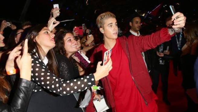 El cantante Justin Bieber se hace un selfie con un grupo de fans que le esperaban en la alfombra roja de los premios MTV EMA 2015.