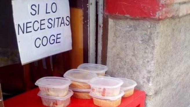 """Imagen de una mesa llena de tuppers con comida sobrante del día que un restaurante de Santander ha decidido ofrecer a aquellos que lo necesiten. Junto a la comida se puede leer en un cartel: """"Si lo necesitas, coge""""."""