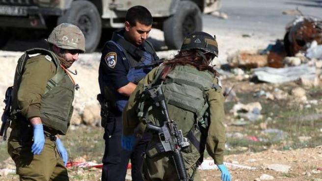 Soldados israelíes inspeccionan el cadáver de un palestino, tras un supuesto ataque.