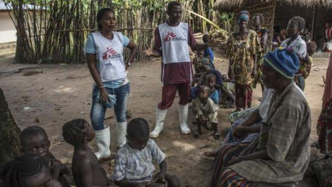 Dos voluntarios hablan a los aldeanos sobre medidas saludables para supervivientes de ébola en el distrito de Tonkilili, en Sierra Leona.