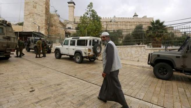 Un fiel pasa delante de las tropas israelíes para participar en el viernes de oraciones en la ciudad cisjordana de Hebrón, Palestina.