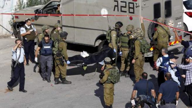 Soldados de Israel retiran el cadáver de un palestino, muerto por disparos de soldados israelíes tras apuñalar a uno de los agentes.