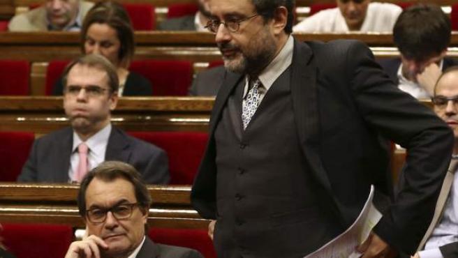 El líder parlamentario de la CUP, Antonio Baños, se dirige a la tribuna de oradores ante el presidente de la Generalitat en funciones, Artur Mas (i).