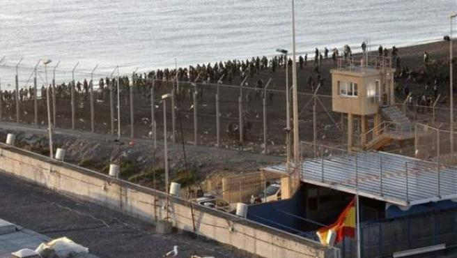 Un grupo de migrantes en territorio marroquí, junto a la valla fronteriza de separación en Ceuta.