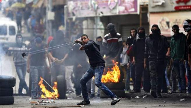 Un joven palestino lanza piedras contra el ejército israelí en la localidad cisjordana de Hebrón.