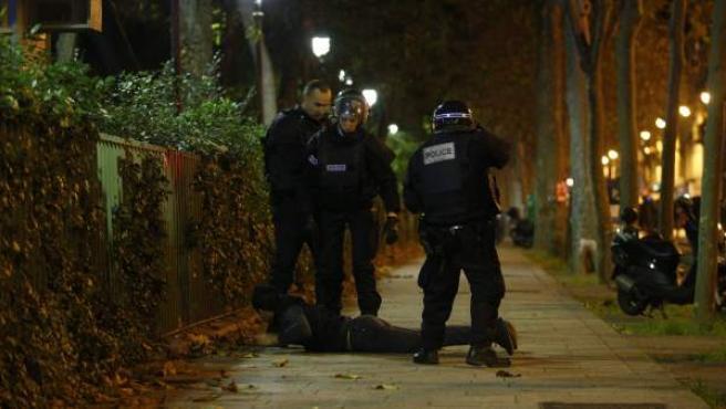 Los agentes de policía detienen a un hombre en la escena de una situación de rehenes en la sala Bataclan en París.