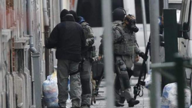 Agentes de policía antidisturbios permanecen en guardia en el distrito de Molenbeek en Bruselas (Bélgica), durante la operación dirigida a encontrar a Salah Abdeslam, sobre quien pesa una orden de arresto internacional.