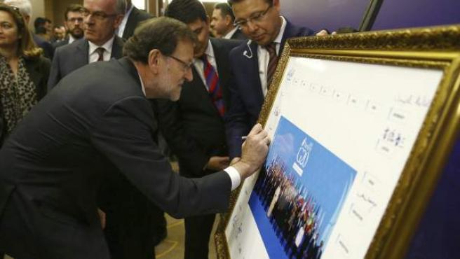El presidente del Gobierno español, Mariano Rajoy, mientras firma en la foto de familia de los asistentes a la décima cumbre del G20 en Antalya (Turquía).