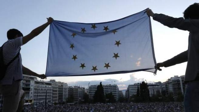 Protestantes sostienen una bandera de la Eurozona y exigen que Grecia permanezca en la Eurozona a las afueras del parlamento griego en Atenas (Grecia).