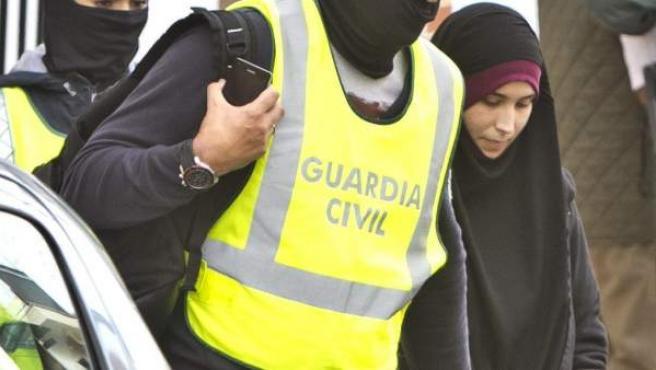 Efectivos de la Guardia Civil acompañados de la joven onubense de 22 años detenida en el aeropuerto de Madrid-Barajas cuando intentaba viajar a Turquía para trasladarse después a Siria e integrarse en Estado Islámico.