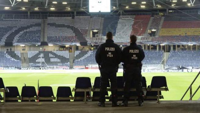 Dos agentes de la policía permanecen en las gradas antes del partido amistoso entre Alemania y Holanda en el HDI-Arena en Hannover (Alemania).