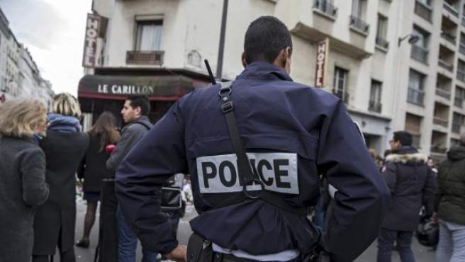 Un agente de policía permanece en guardia ante el bar le Carillon de París, Francia.