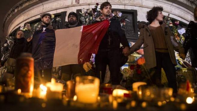 Varias personas cantan el himno nacional francés en la plaza de la República de París, Francia.