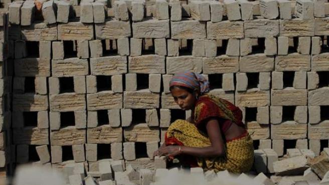 Una india trabaja en una fábrica de ladrillos en Rajabari (India)