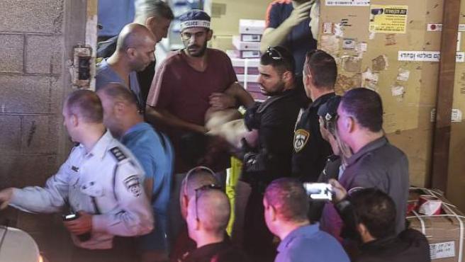 Agentes de policía detienen a un palestino en el lugar del ataque perpetrado en Tel Aviv, Israel.