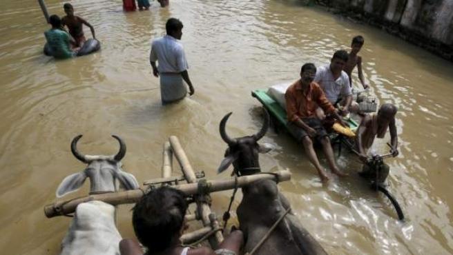 Varias personas cruzan las calles anegadas de la localidad de Prafulla Nagar, a 120 kilómetros de Calcuta, India.
