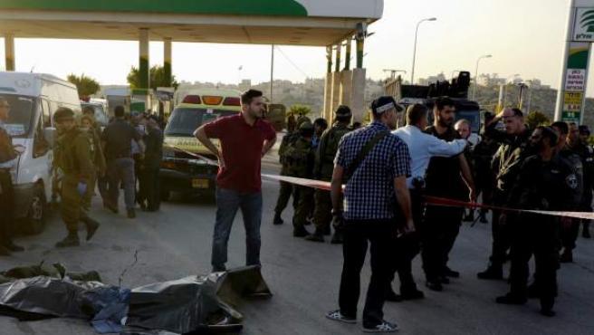 Varios militares israelíes permanecen junto al cuerpo sin vida de un palestino abatido en la estación de servicio 443 de Cisjordania tras apuñalar y matar a un joven israelí.