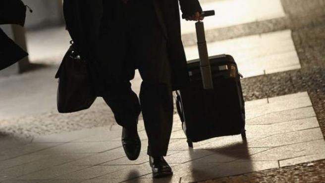Un hombre con una maleta de mano por un aeropuerto.