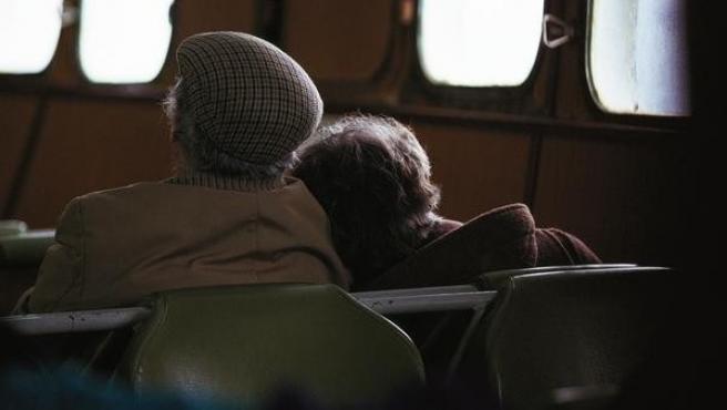 Una pareja de jubilados, sentados en un vagón de tren.