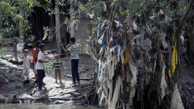 Varios niños indonesios juegan con bolsas de plástico y otros desechos inorgánicos que cuelgan de un árbol en la ribera del río en Medan, Sumatra del Norte (Indonesia).