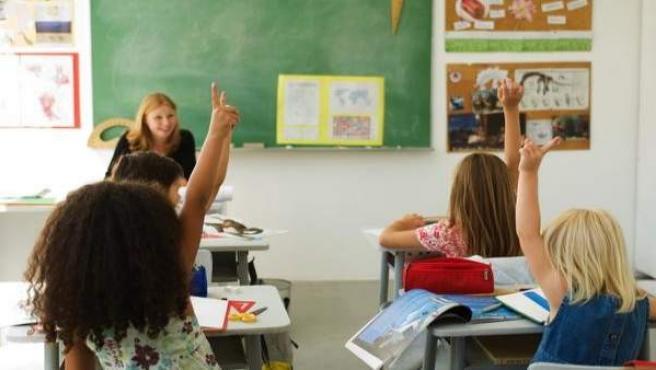 Varios niños con las manos levantadas durante una clase.