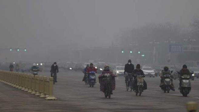 Motoristas y ciclistas usan mascarillas para protegerse de la contaminación mientras circulan por una calle de Pekín.