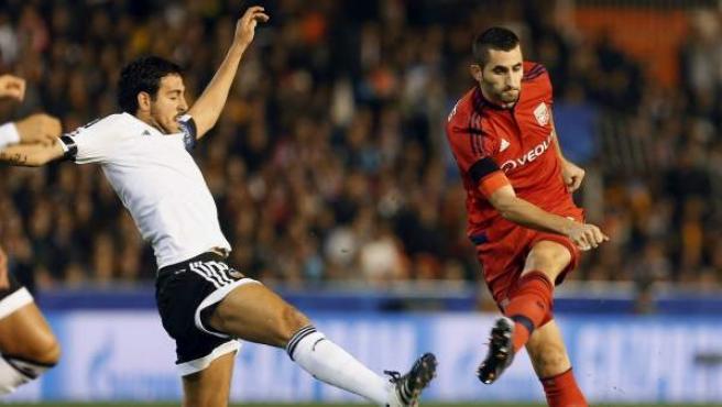 Parejo intenta impedir el disparo de Gonalons en el Valencia - Olympique de Lyon.